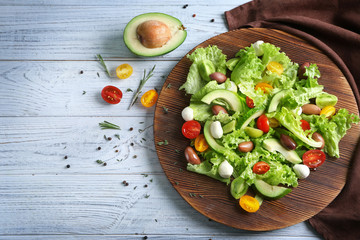 Wooden board with delicious vegetable salad on table, closeup