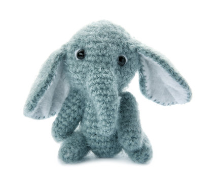 Cute knitted toy elephant on white background