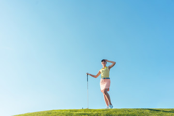 Low-angle view of a fit and cheerful woman wearing golf trendy outfits, while looking away during practice on the green grass of a professional golf course