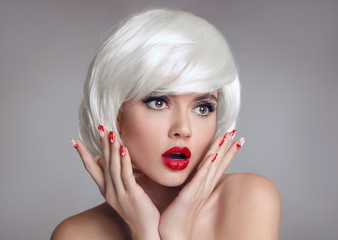 Shocked face. Blond Woman with red lips and manicure nails surprise holds cheeks by hand. Beautiful girl with white short bob hairstyle isolated on gray background. Expressive facial expressions.
