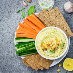 Vegan healthy hummus in a bowl and vegetable sticks crisps on stone or concrete background.  Top view,space for text.