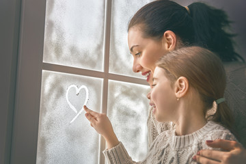 family drawing a heart on frozen glass