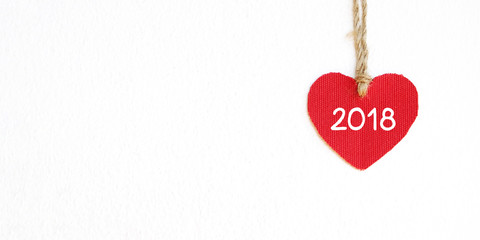 Red fabric heart shape with 2018 word hanging over white wall background, new year template banner