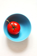 Red vegetable tomato in a blue bowl