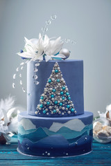Tiered cake the blue cake with the image of a Christmas tree and white flowers on top. Concept of festive desserts