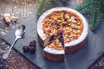 Homemade Christmas or New Year holiday berry pie with nuts on wooden table background. Concept of festive desserts
