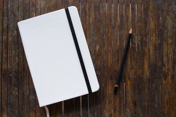 White cover notebook with black pencil on rustic wooden table flat lay photo.