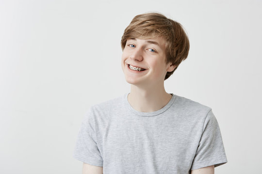 Cheerful fair-haired young man with braces grins at camera, has overjoyed expression, clenches teeth, being glad to pass all exams at university. Positive feelings and emotions.