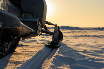 A snowmobile stands on the snow at sunset.