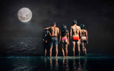 Group of friends taking night bath in the ocean