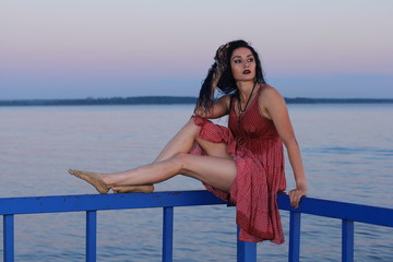 Young woman in red wet dress relaxing on pier on the sea at sunset.