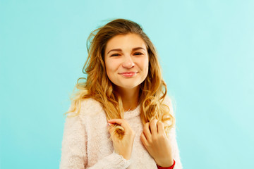 Young happy woman in warm sweater over blue background