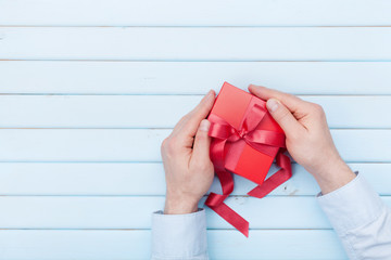 Man holds a gift box in hands on Valentines day or Christmas. Top view and copy space for text.