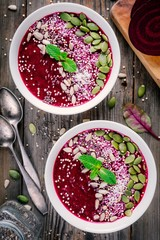 Beet smoothie bowl with chia seeds, coconut, pumpkin seeds, quinoa, sunflower seeds and mint