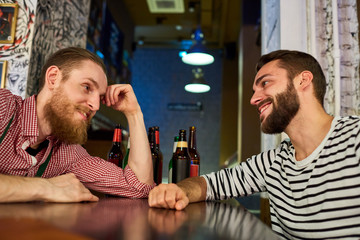 Side view portrait of two smiling young men chatting casually at table in bar and drinking beer, copy space