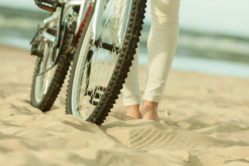 Unrecognizable woman bike cycling on sand