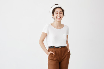 Pleased pretty woman with dark and wavy hair in bun, dark eyes and healthy skin dressed in white T-shirt and brown trousers holding hands in pockets, posing against white background.