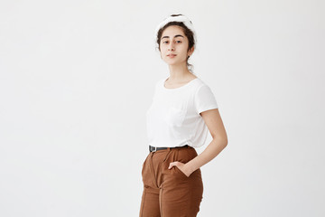 Attractive young female model with dark and wavy hair in bun, wearing white t-shirt and trousers, keeping her hands in pockets, posing against white background with copy space for advertisment