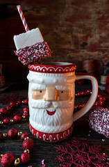 Santa mug of hot cocoa with peppermint marshmallows in festive setting