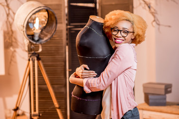 Portrait of a young african fashion designer with mannequin at the tailoring studio