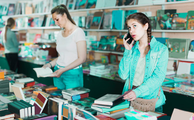 Girl 10-15 years old is choosing book while calling
