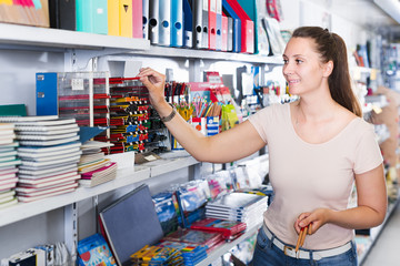 Smiling female buying products in stationery shop