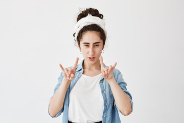 Positive gloomy young girl with dark and wavy hair in bun, wearing do-rag having fun, pouting lips, showing rock sign with both hands. Body language and gestures concept.
