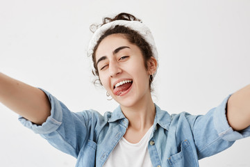 Happiness, beauty, joy and youth. Young positive girl dressed in denim shirt over white t-shirt stretching arms, smiling broadly, blinking, sticking out her tongue, having good mood.
