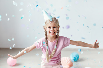Joyful smiling blonde female kid with two pigtails, wears festive hat, tries to catch flying papers in air, has fun, being in high spirit as celebrates mother`s birthday. Childhood, holidays concept