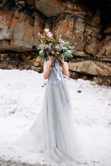 Woman stands on the road in snowy mountains in grey wedding dress with a face hidden behind a chic bouquet
