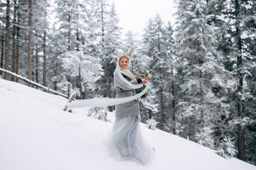 Beautiful woman stands on the snowy pine forest in grey wedding dress with bouquet in hands and long veil