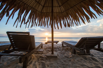 Sun loungers with umbrella on the beach, sunrise