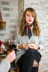 Girl having a cup of mulled wine at home