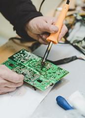 Man Repairing Electronic Circuitr using welder tool