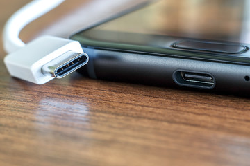 New fast USB Type-C port on mobile phone and cable close-up