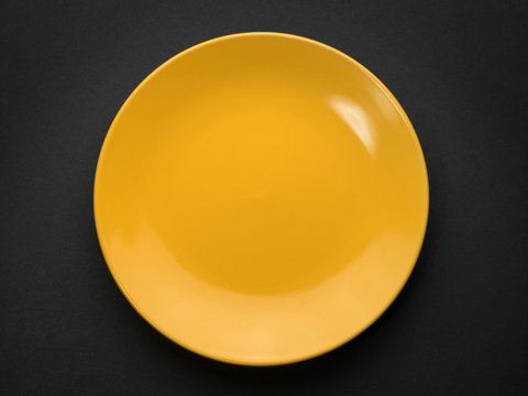 Empty yellow plate on black