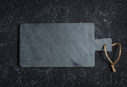 Black old-fashioned stone and slate cutting board on black background