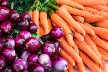 carrots and purple red onion on farmers market