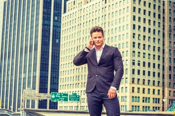 American businessman traveling, working in New York. Dressing in black suit, a young, strong, sexy professional standing in business district, listening, talking on mobile phone..