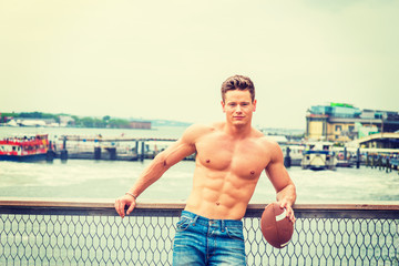 American Man's Beauty in New York. Shirtless, half naked, waring jeans, a young sexy guy casually standing by fence at harbor, holding football, looking at you, enjoying hot summer..