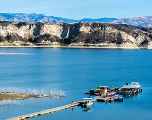 long wooden pier with boats at California's Lake Cachuma with San Rafael Mountains in the distance