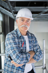 senior builder holding stairs on grey background