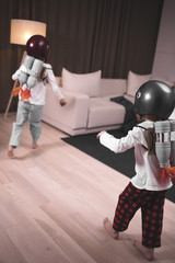 Funny cute dreamer siblings wearing helmets and rocket packs made from plastic bottles pretending to be astronauts, jumping from sofa into space