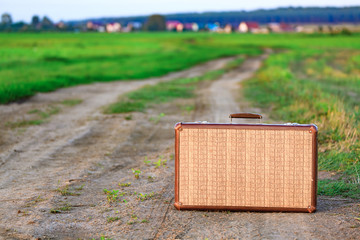 Retro styled old suitcase on a countryside road