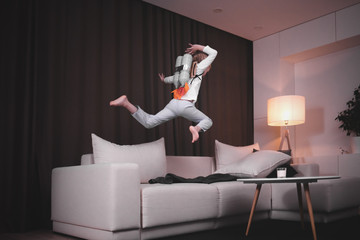 Funny cute dreamer girl wearing rocket pack made from plastic bottles jumping into space from sofa
