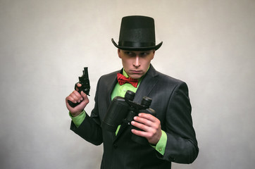 Spy agent. Secret service. Detecive agent holds pistol gun in his hands and binoculars isolated. Retro gangster.