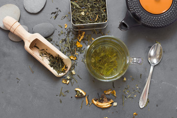 cup of green tea and dried tea on grey stone table