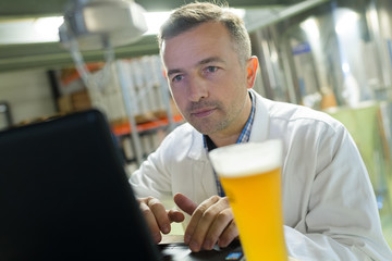 man on laptop drinking beer