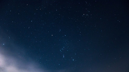 Constellation of the orion on a beautiful, night, starry sky with clouds.