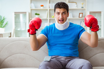 Man with neck injury watching boxing at home